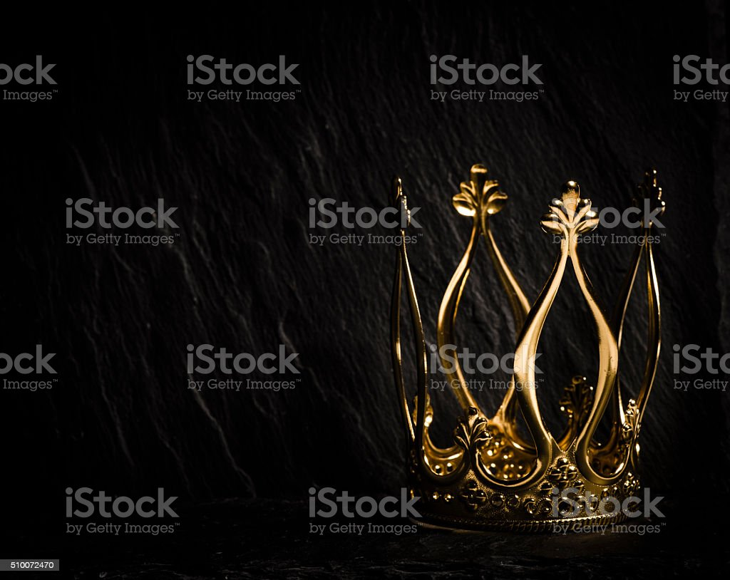 Golden crown with dark background stock photo