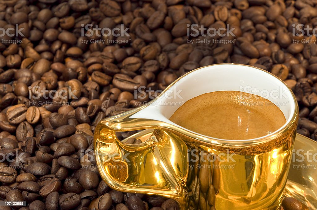 Golden cup of coffee on beans royalty-free stock photo
