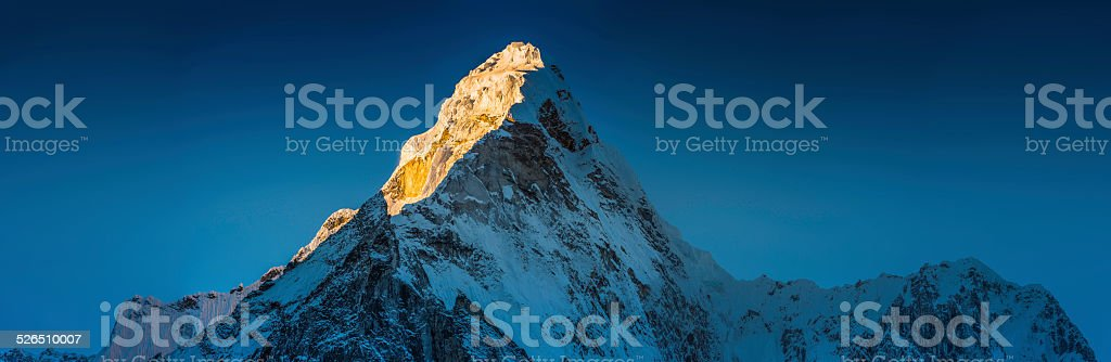 Golden dawn light on idyllic snowy mountain peak panorama Himalayas stock photo