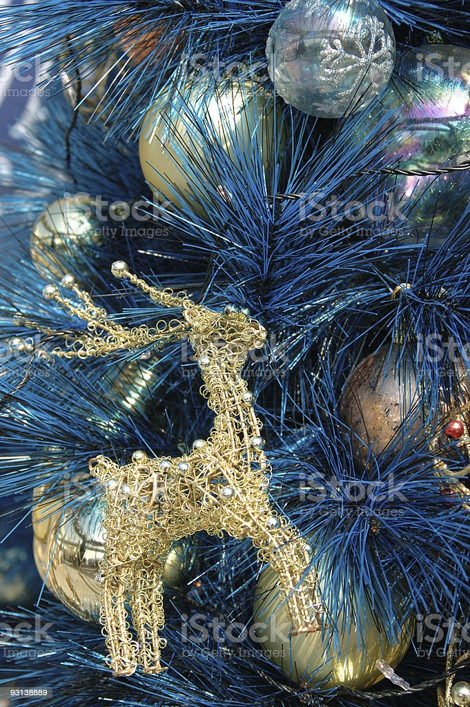 Golden deer ornament on blue christmas tree royalty-free stock photo