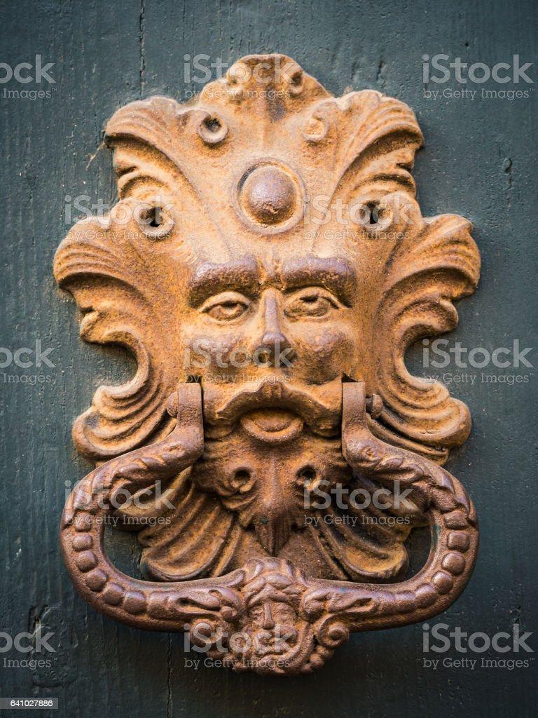 Golden door knocker of an old door in Italy. stock photo