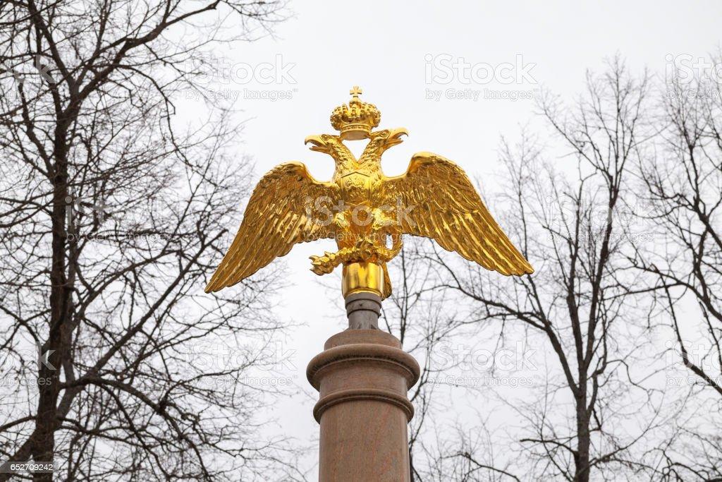 Golden Double Eagle on stone column stock photo