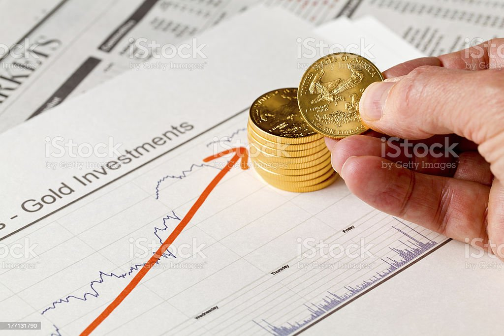 Golden Eagle coins on newspaper stock photo