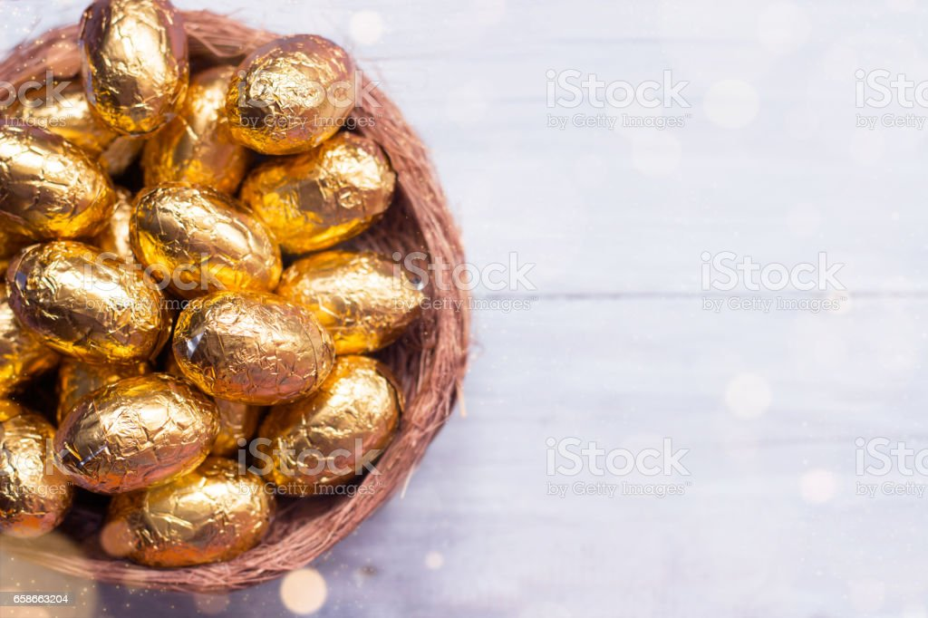 Golden easter eggs  - chocolate eggs in nest, on white wooden background stock photo