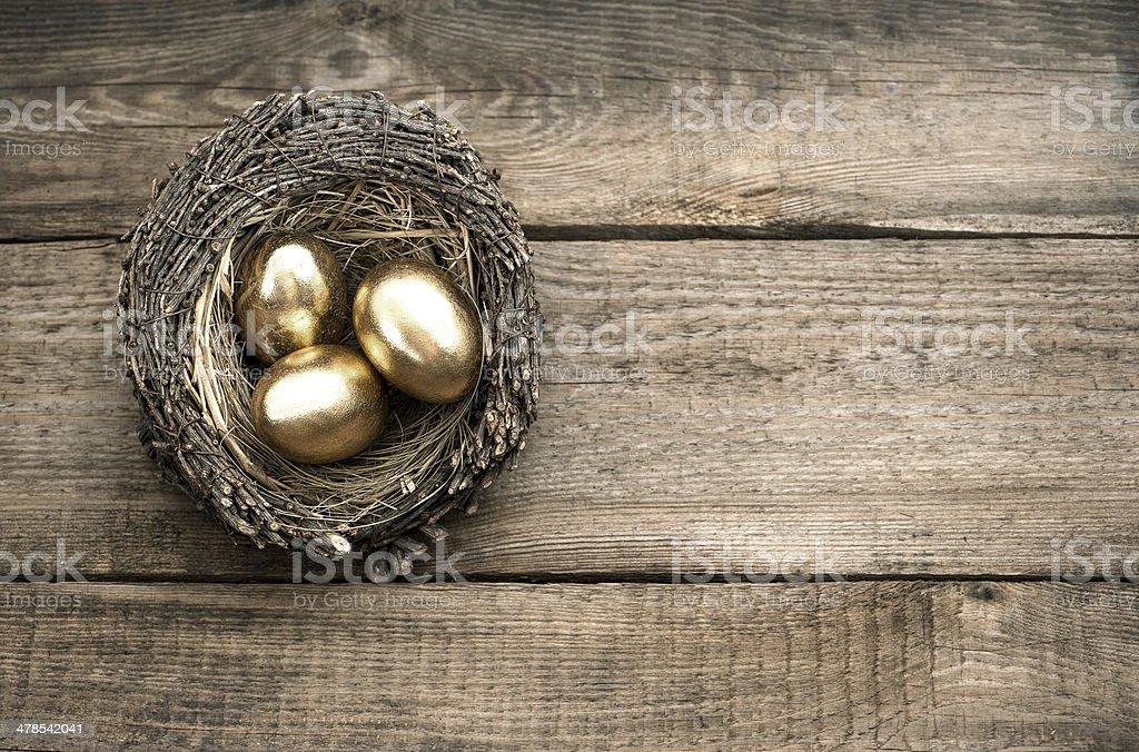golden easter eggs over wooden background stock photo