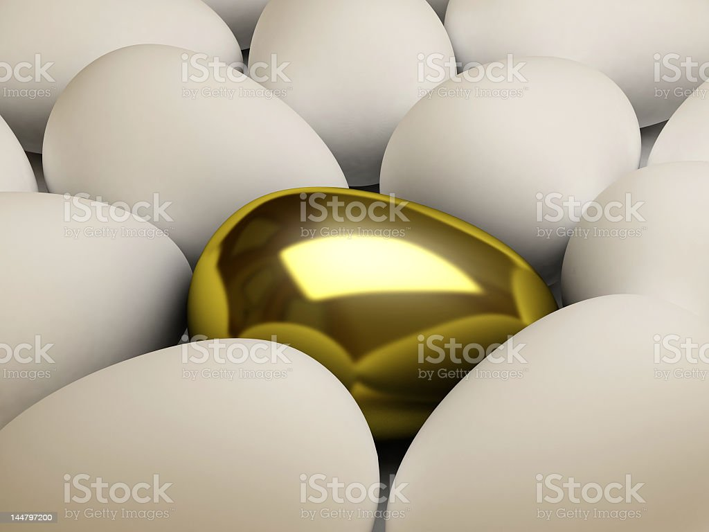 Golden egg amongst normal eggs representing uniqueness royalty-free stock photo