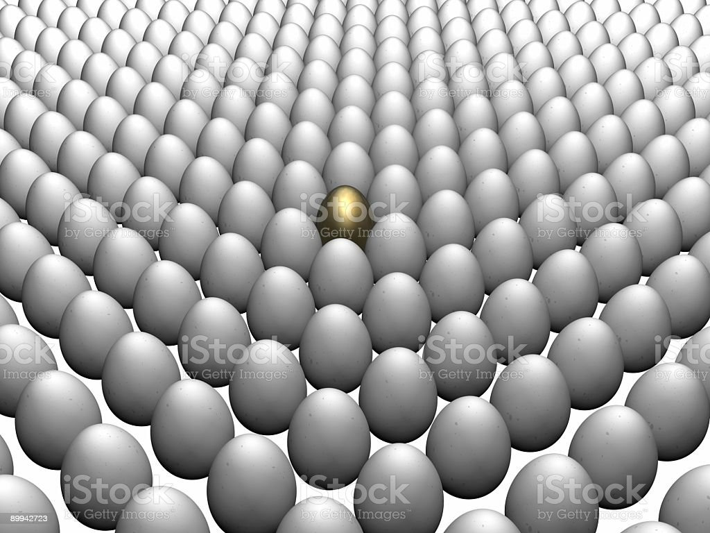 Golden egg nestled among white eggs stock photo