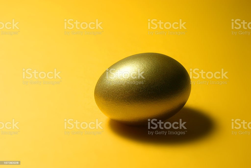 Golden Egg on Yellow Background royalty-free stock photo
