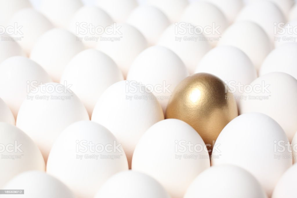Golden Egg Standing Out from a Crowd of Ordinary Eggs stock photo