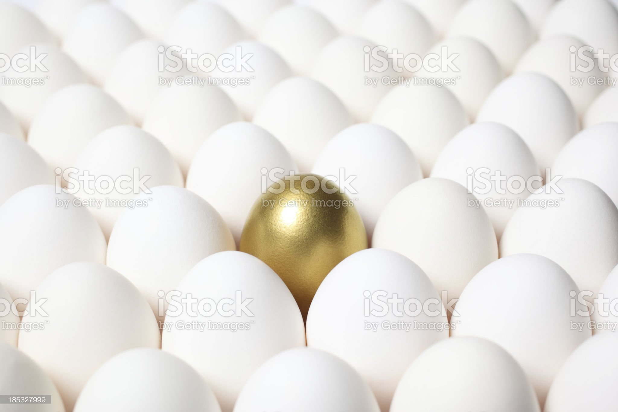 Golden Egg Standing Out from a Crowd of Ordinary Eggs royalty-free stock photo