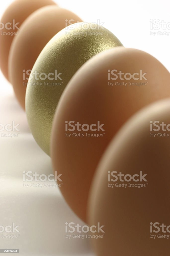 Golden Egg Standing Out from the Crowd of Ordinary Eggs royalty-free stock photo