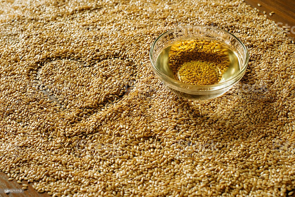 Golden flax seeds and a bowl of oil stock photo