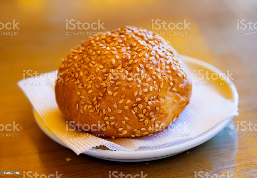 Golden fresh bun with sesame seeds on white plate stock photo