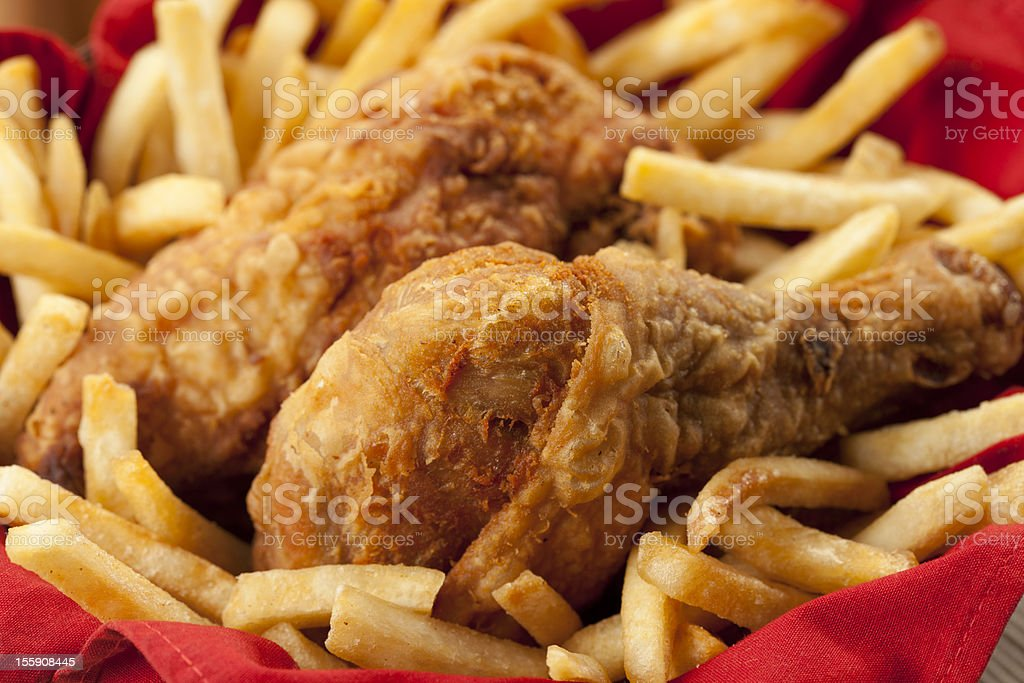 Golden fried chicken on a bed of French fries and red napkin stock photo