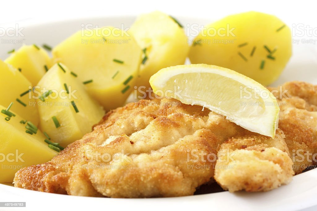 Golden fried schnitzel with boiled potatoes stock photo