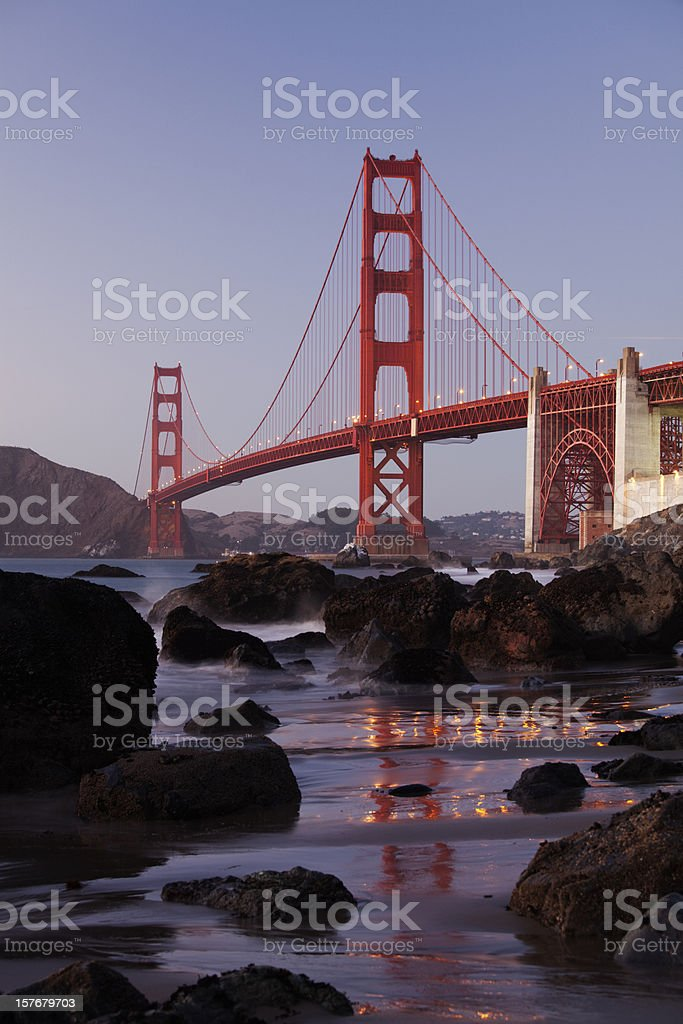 Golden Gate Bridge with reflections in sand after sunset stock photo