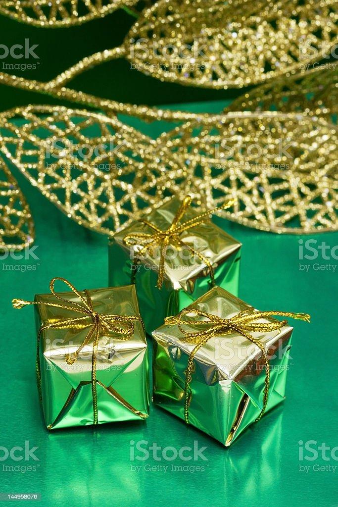 Caixas de presente ouro sobre fundo verde com folha foto de stock royalty-free