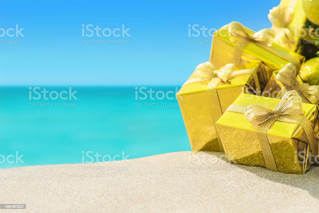 Golden gift boxes with bows close-up at tropical ocean beach stock photo