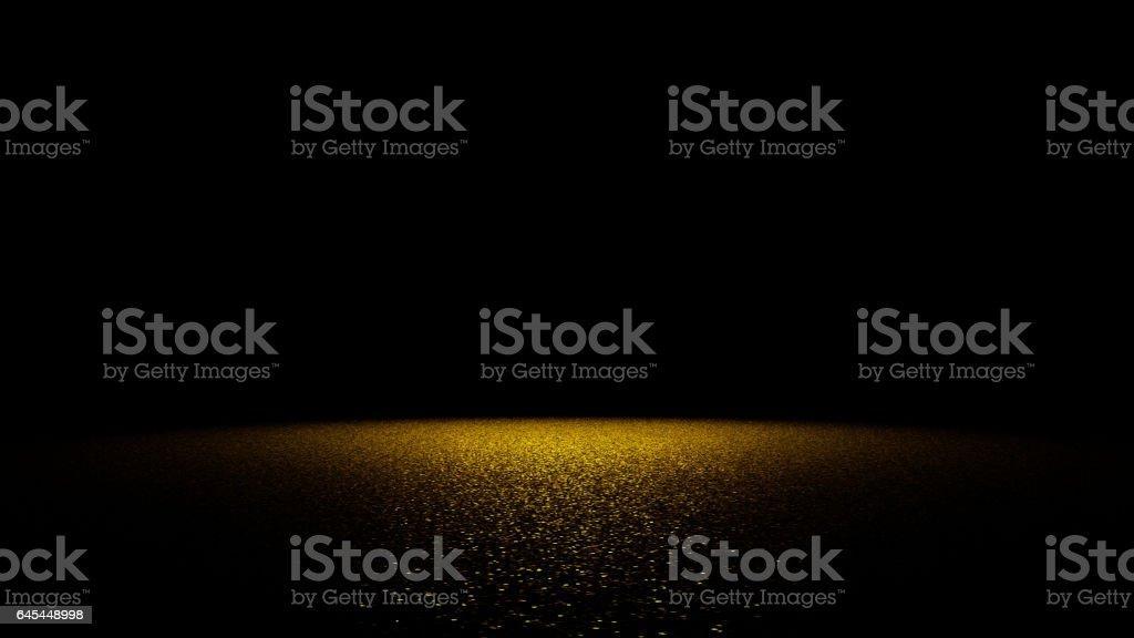 golden glitter on a flat surface lit by a bright spotlight stock photo