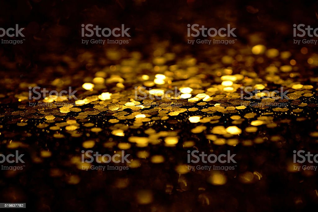 Golden glitter on black background stock photo