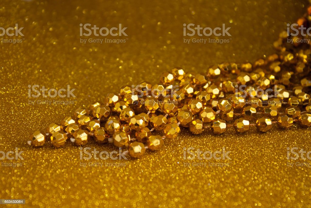 golden glitter paper and gold colored necklace beads texture and backgrounds stock photo