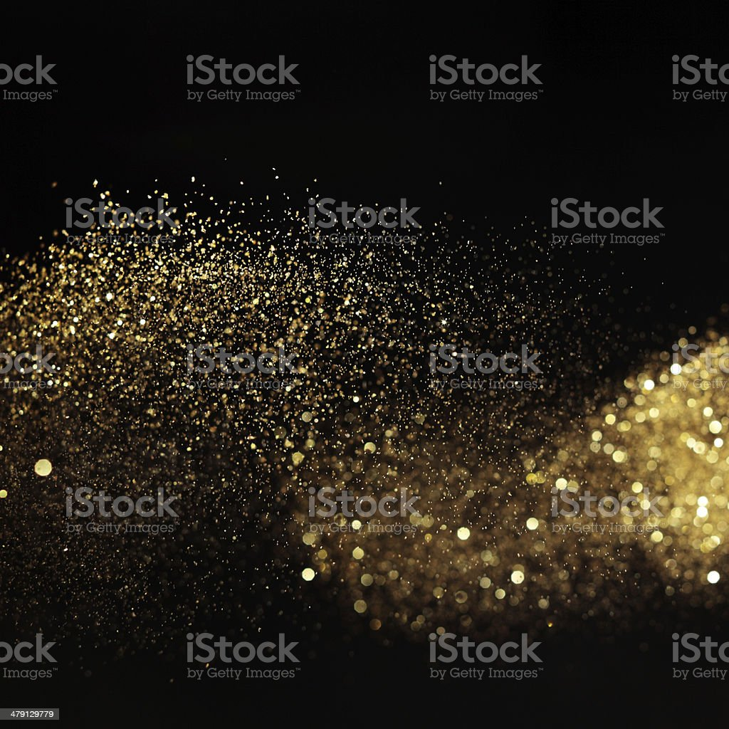 Golden glittery light on black background stock photo