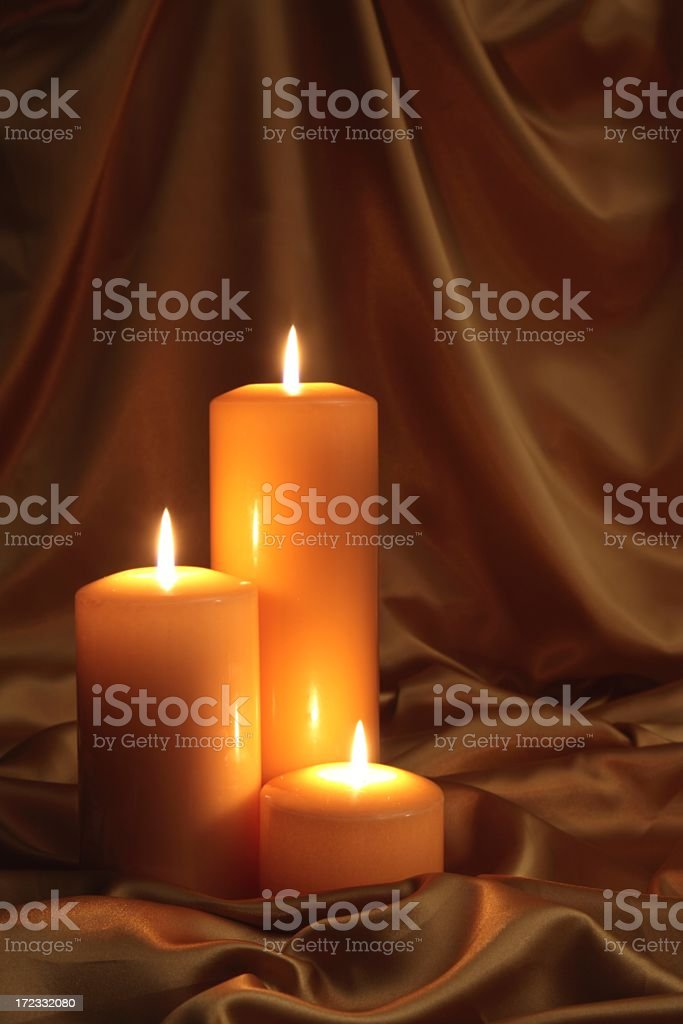 Golden Glow of three burning candles on satin royalty-free stock photo