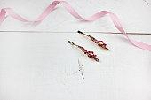 Golden hairpins with pink gemstone on pink background