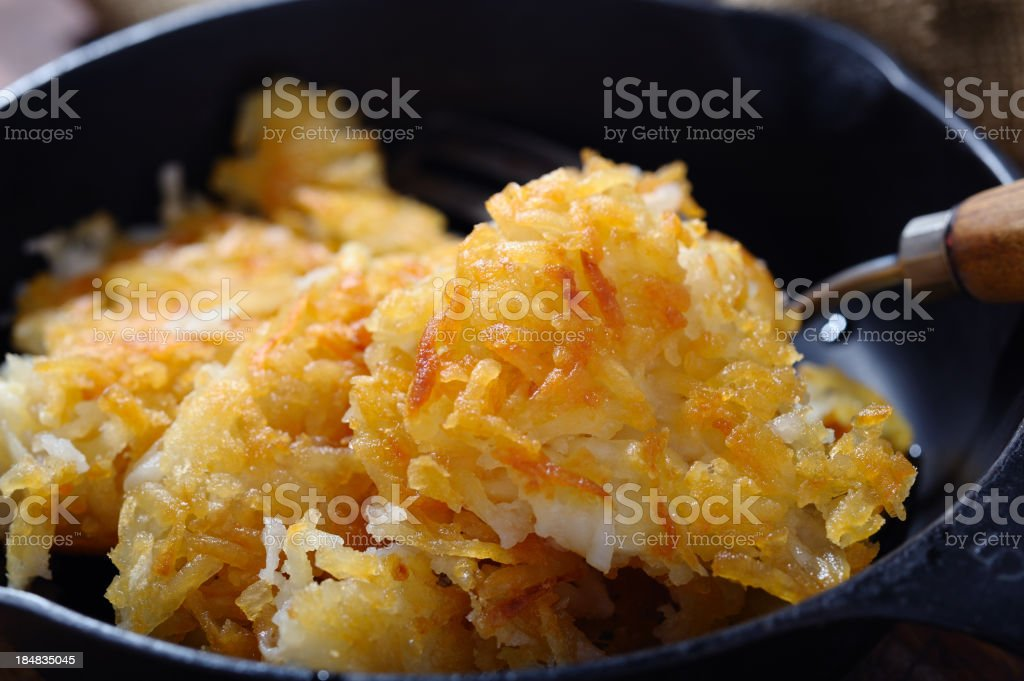 Golden hash browns in black frying pan stock photo