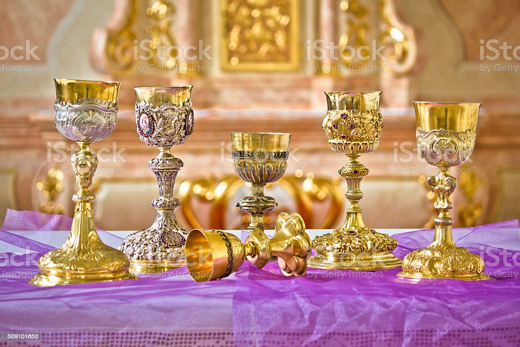 Golden holy grails on church altar view stock photo