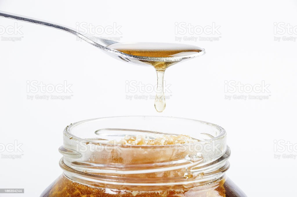 Golden honey dropping from spoon in jar royalty-free stock photo