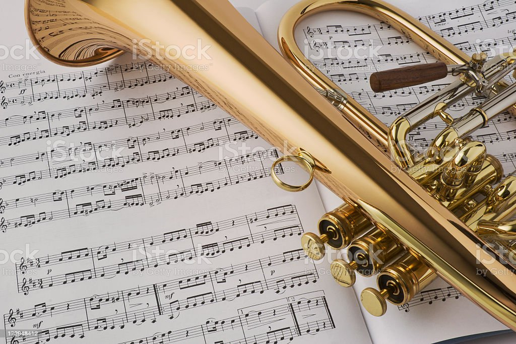 Golden horn laying on sheet music royalty-free stock photo