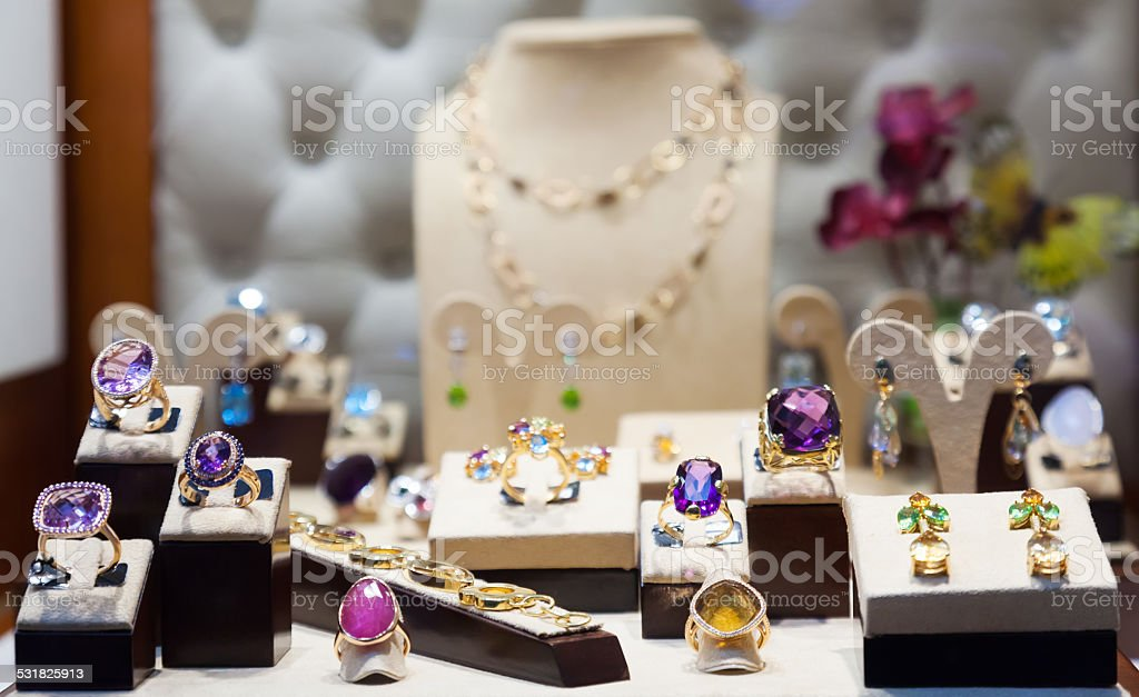 Golden jewelry with gems at showcase stock photo