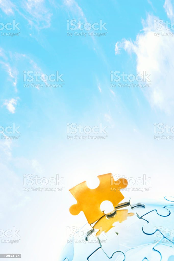 Golden jigsaw piece against bright sky royalty-free stock photo