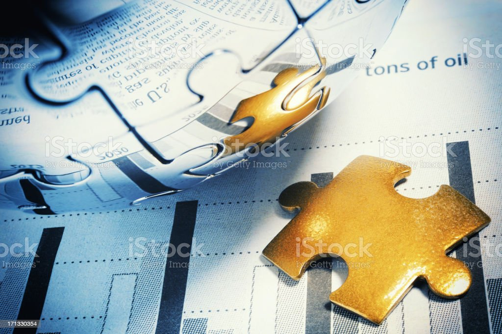 Golden jigsaw piece on financial page stock photo