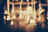 Golden jingle bells hanging in the dark background