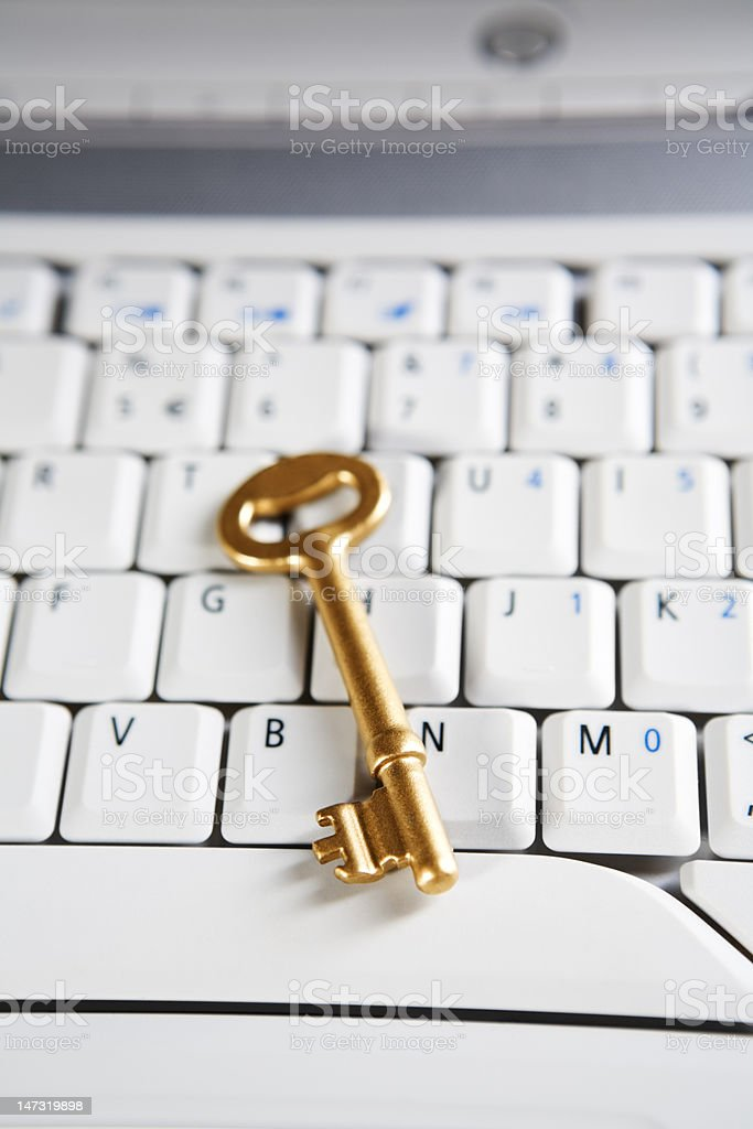 Golden key on laptop royalty-free stock photo