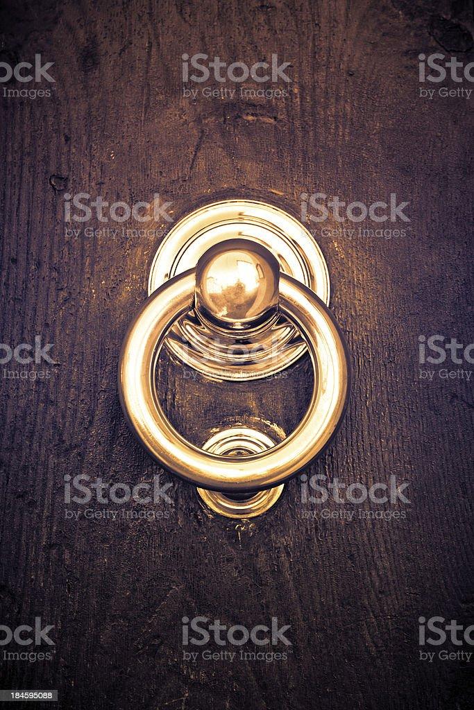 Golden Knocker on Dark Wooden Door stock photo