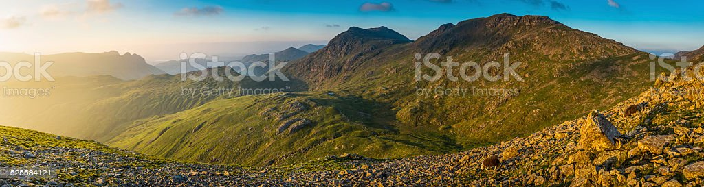 Golden light filling mountain valley panorama Lake District fells UK stock photo