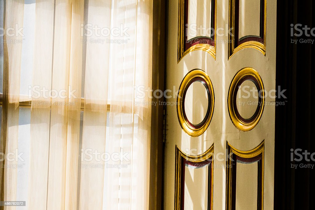 Golden light from window through curtains to gilded shutters stock photo