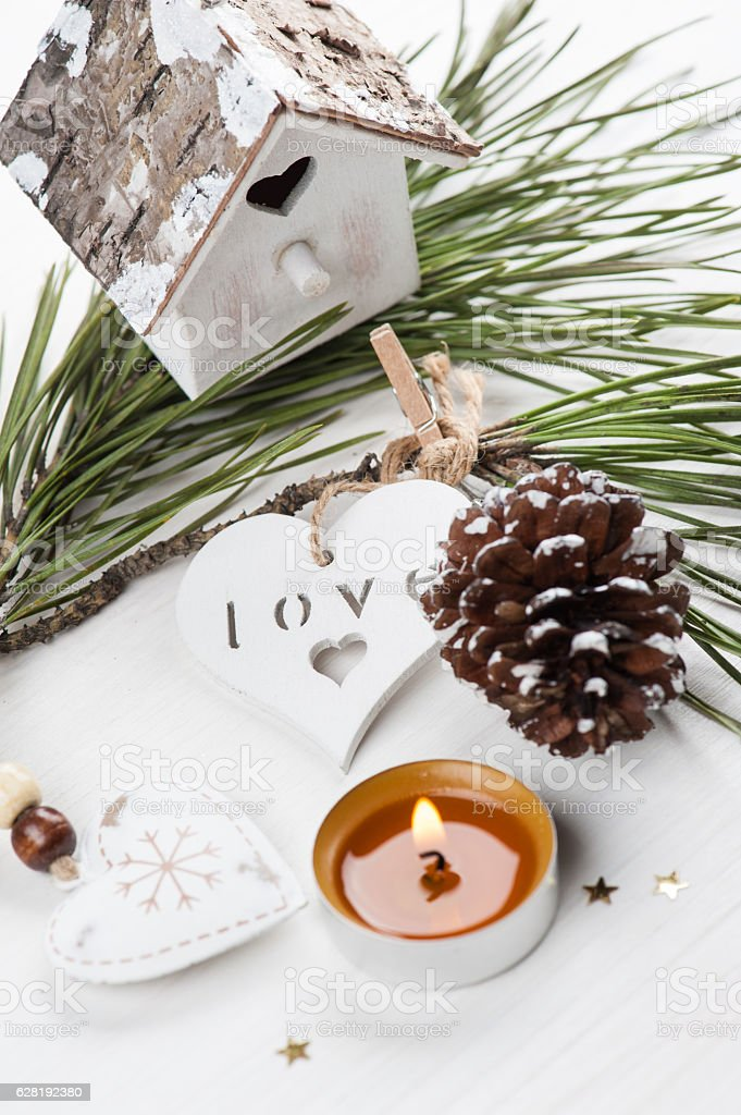 Golden lit candle, wooden christmas toys stock photo