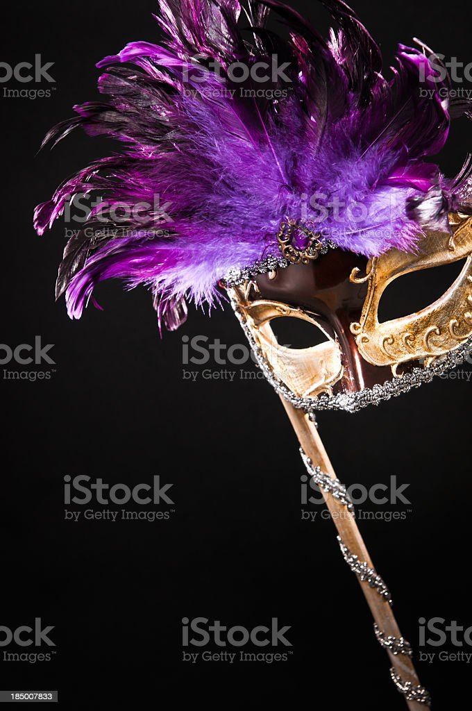 Golden masquerade carnival mask with purple feathers royalty-free stock photo