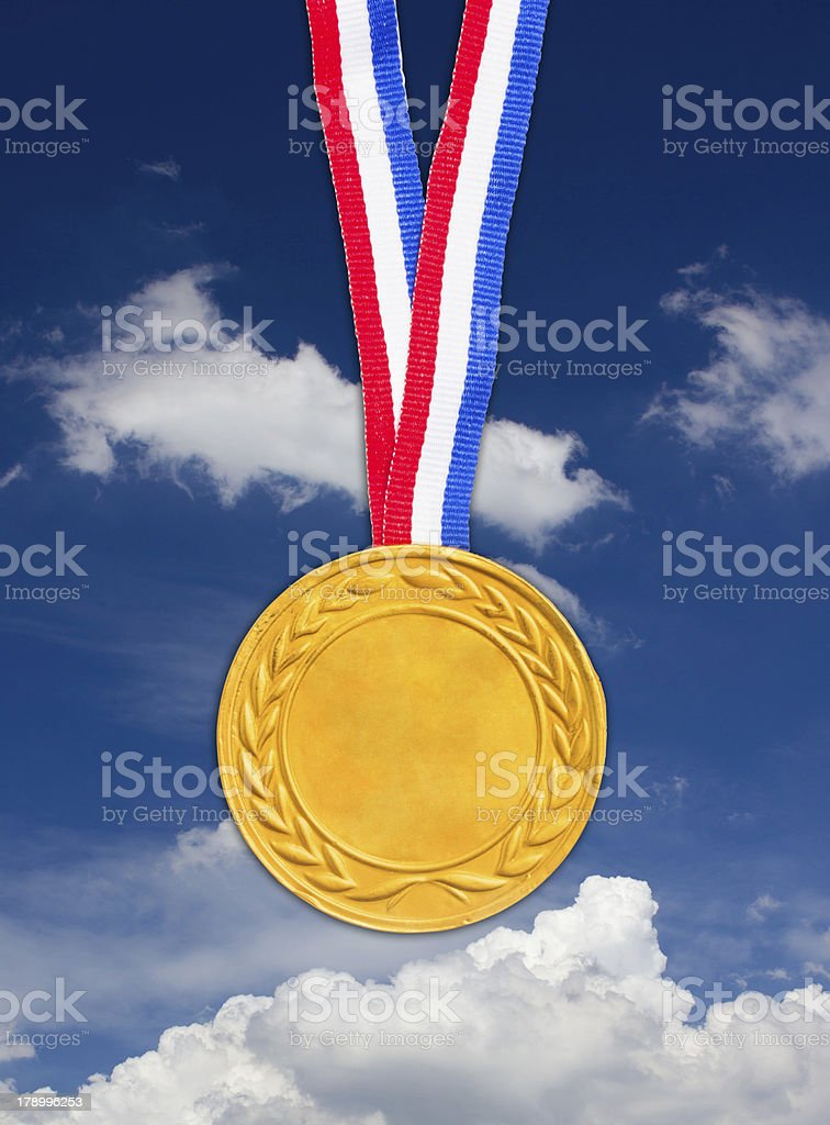 Golden medal in front of blue sky. royalty-free stock photo