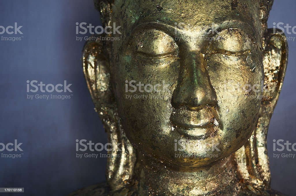 Golden Meditating Buddha Statue Textured Face Close-Up royalty-free stock photo