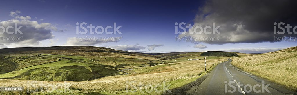 Golden moorland view with an open road and blue sky stock photo