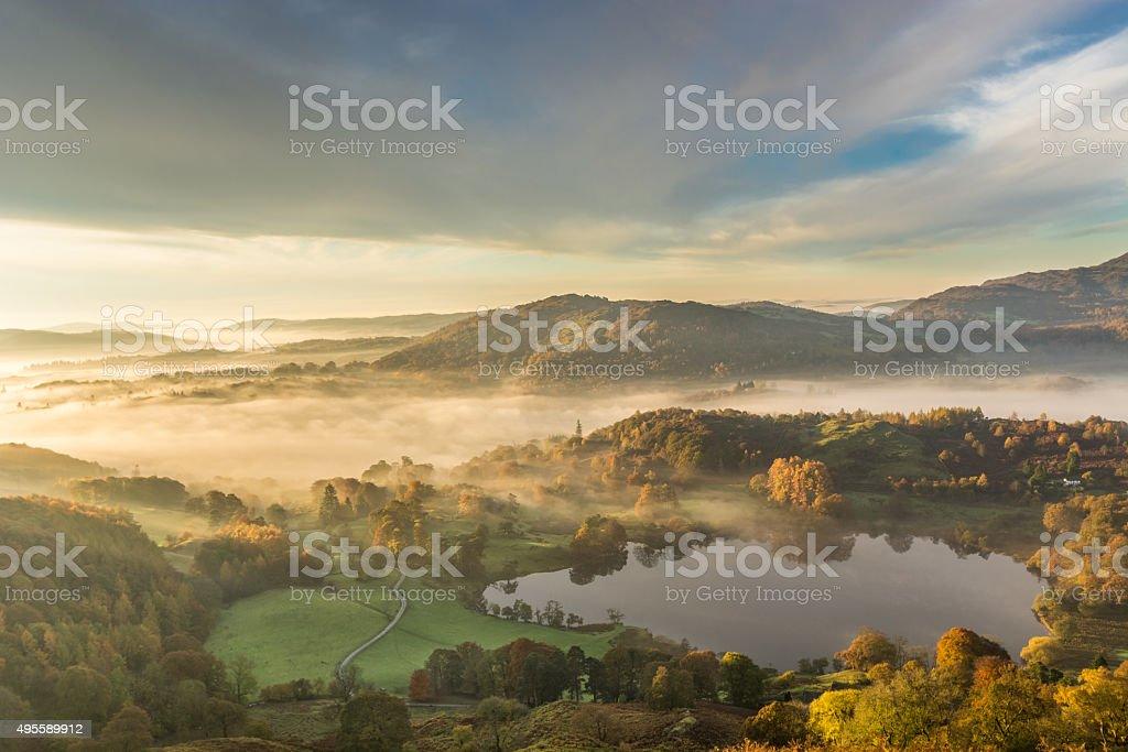 Golden Morning Light Shining Across Lingering Fog In Langdale Valley. stock photo