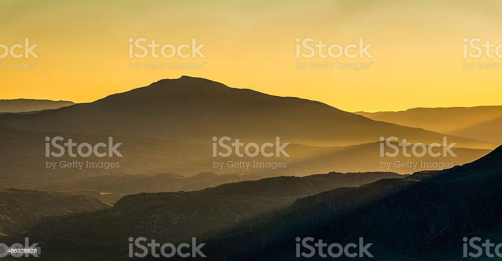 Golden mountain sunrise rays of light over Highlands Assynt Scotland stock photo