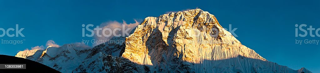 Golden mountain sunset snow summit Chamlang glacier pinnacles panorama Himalayas stock photo