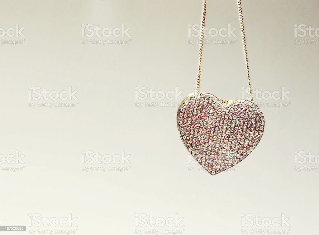 Golden necklace in a shape of heart with precious diamonds stock photo