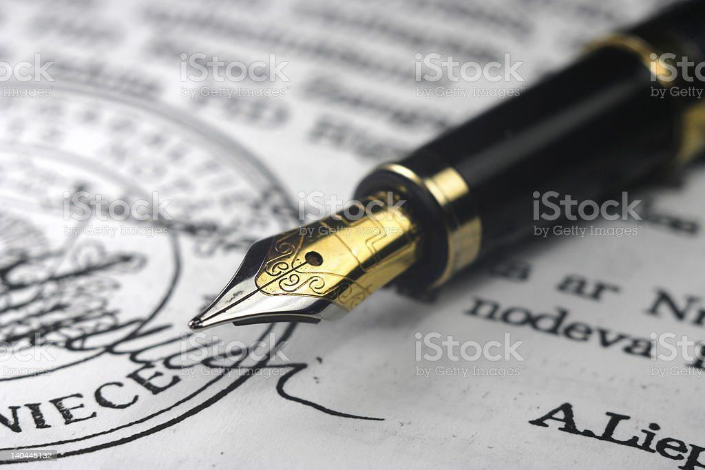 Golden nib pen on document royalty-free stock photo